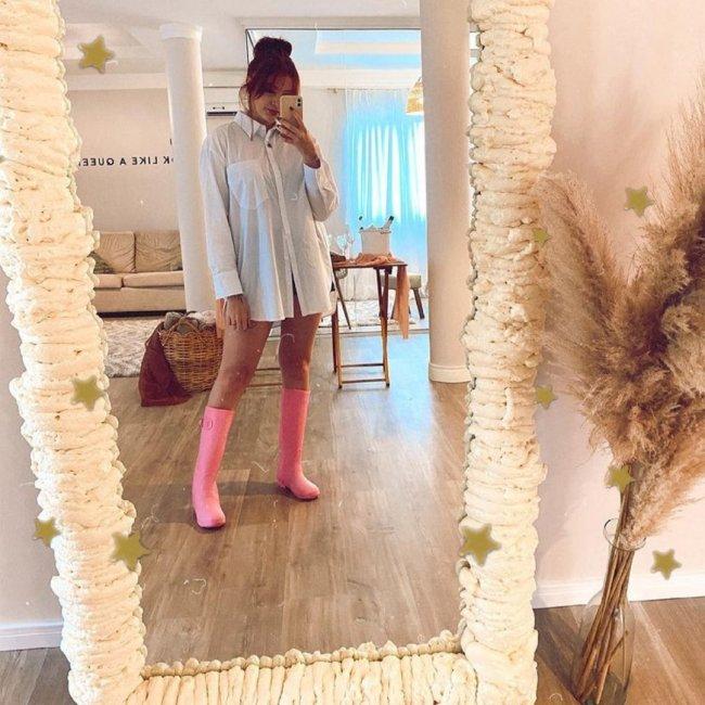 Jovem posando em frente a espelho e tirando selfie, usando coque, bota rosa e camisa branca.