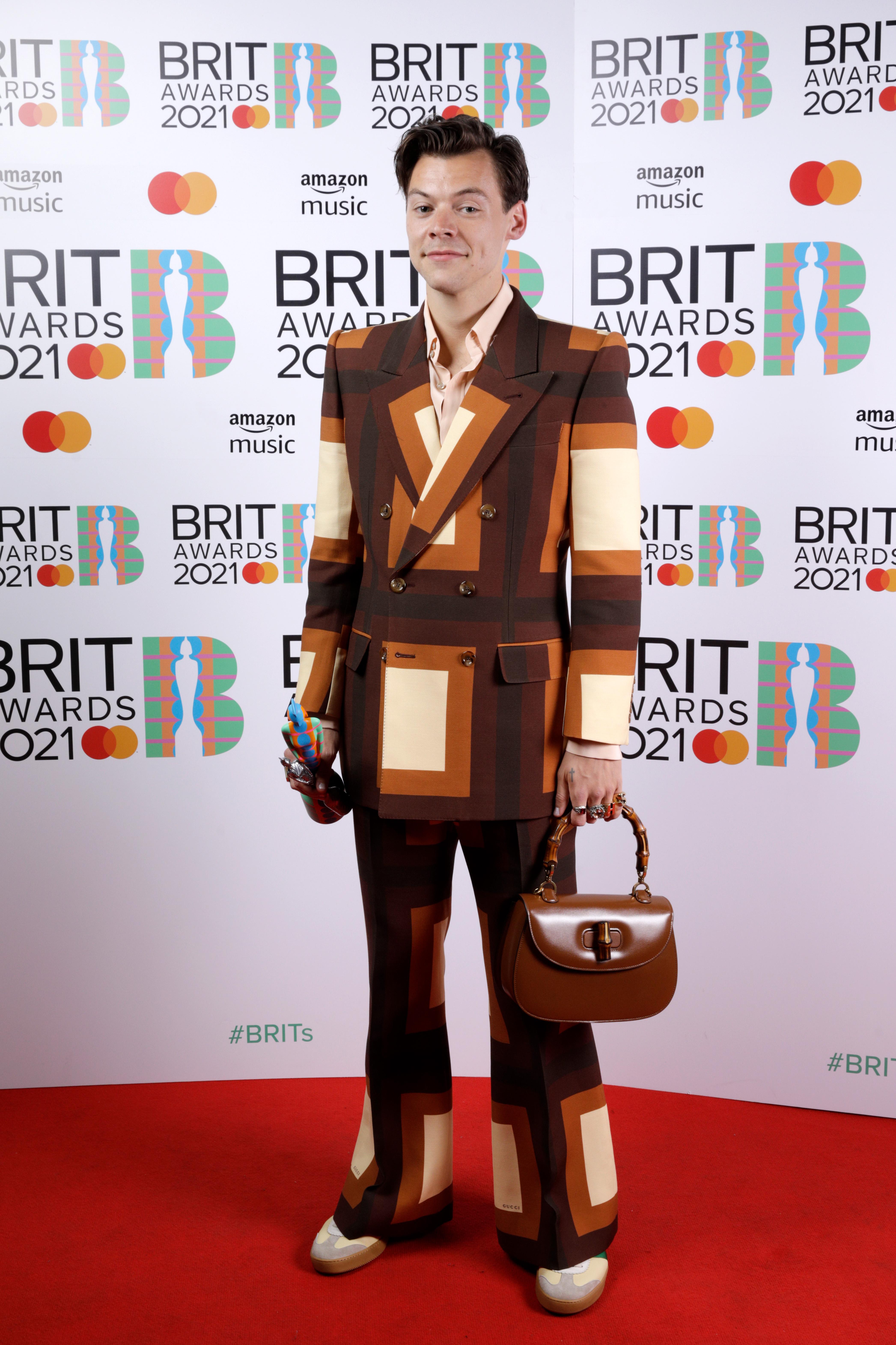Harry Styles no tapete vermelho do BRIT Awards 2021. Ele está usando um terninho com xadrez em tons de marrom e bege. Com uma das mãos, ele segura uma bolsa marrom de alça curta, e com a outra uma estatueta da premiação. Ele está sorrindo levemente olhando para a câmera.Harry Styles no tapete vermelho do BRIT Awards 2021. Ele está usando um terninho com xadrez em tons de marrom e bege. Com uma das mãos, ele segura uma bolsa marrom de alça curta, e com a outra uma estatueta da premiação. Ele está sorrindo levemente olhando para a câmera.