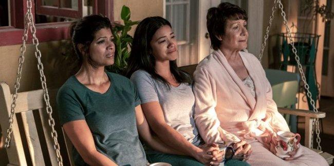 Três personagens femininas de Jane The Virgin sentadas de frente para uma luz emocionadas.