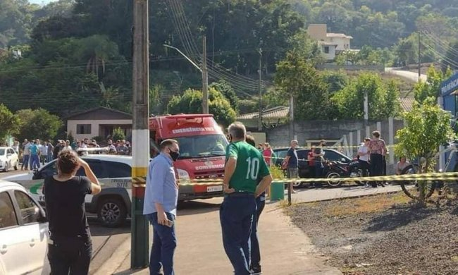 A imagem mostra um homem de camisa azul conversando com outro homem de camisa verde. Ao fundo, está uma ambulância na porta de uma escola e um grupo de pessoas