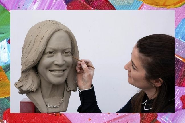 A imagem mostra uma mulher, usando uma blusa preta de manga comprida, esculpindo o rosto da estátua de Kamala Harris