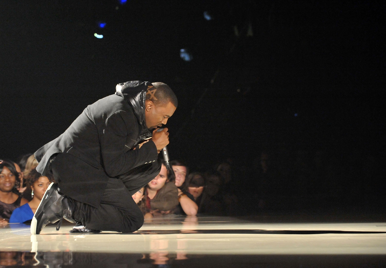 Kanye West no palco do Grammy de 2008. Ele veste um casaco com capuz preto, calça preta e tênis de couro preto com cano alto. Ele está ajoelhado e cantando com o microfone na mão direita.