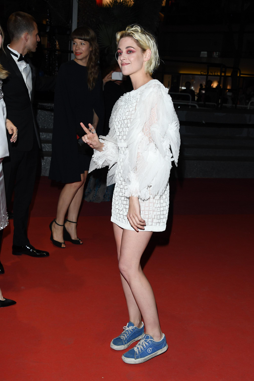 Foto da atriz Kristen Sttewart no tapete vermelho do Festival de Cannes em 2019. Ela usa um vestido branco de renda com mangas bufantes e um tênis azul da marca Vans. Ela caminha e sorri para a foto.
