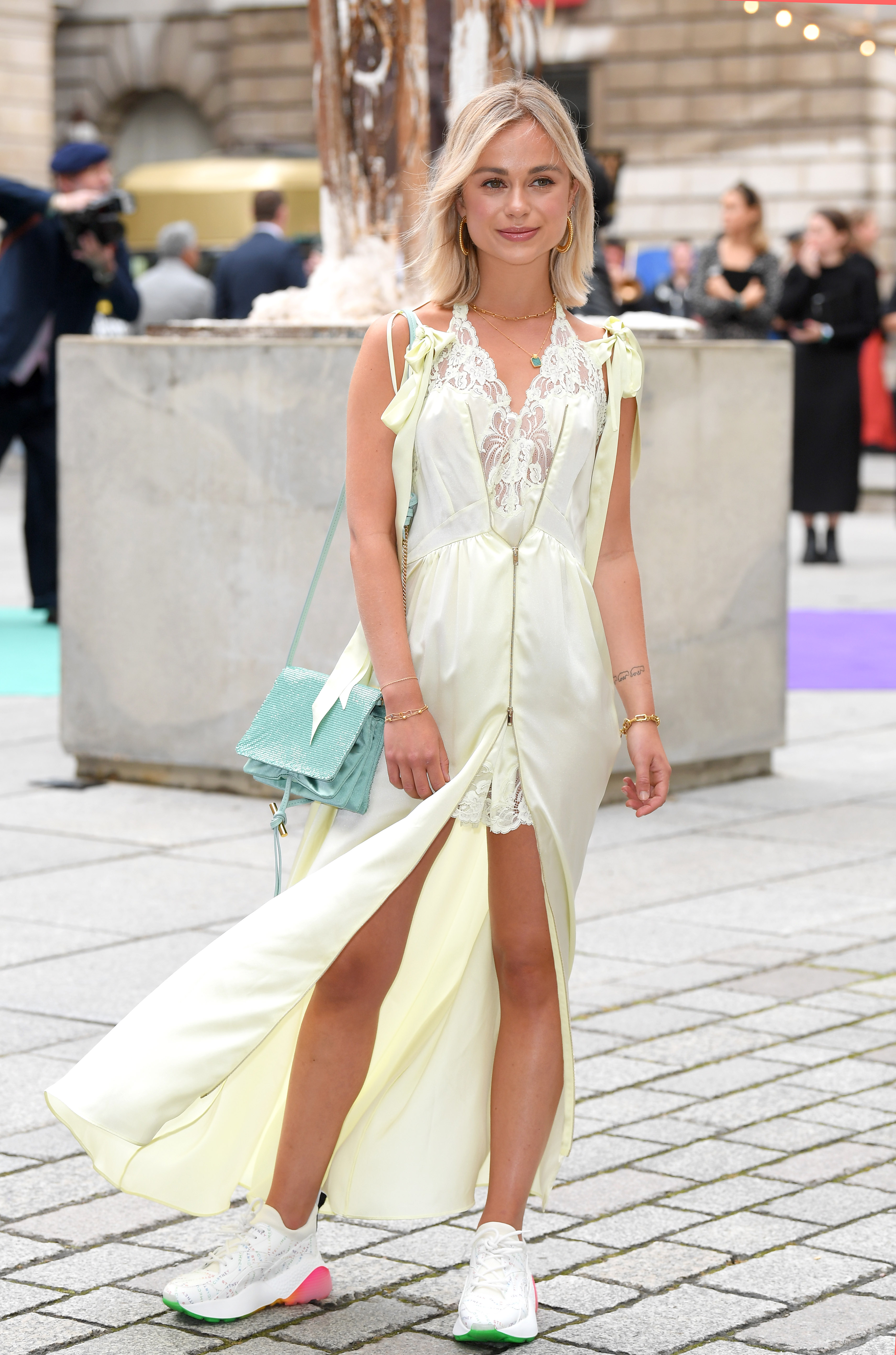 Foto da Lady Amelia Windsor no tapete vermelho da exposição de verão da Royal Academy of Arts. Ela usa um vestido de renda na cor verde menta com laços no ombro, bolsa azul e tênis branco com detalhes rosa e verde. Ela olha para o lado e sorri.