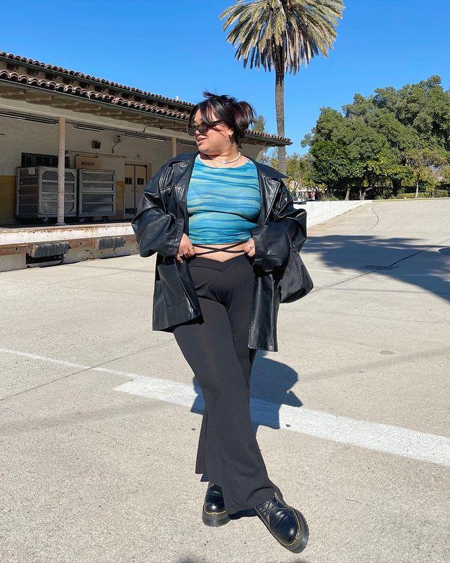 Foto de uma mulher na rua. Ela usa uma jaqueta de couro preta, blusa azul, calça legging bailarina, coturno e um óculos de sol vintage. Ela está com as mãos na cintura e olha para o lado.