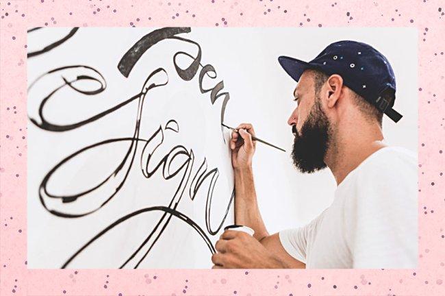 Um homem barbudo e de boné desenha algumas letras cursivas, conhecidas como lettering, numa parede branca