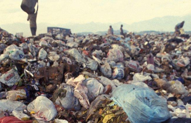 Imagem de um lixão a céu aberto; ao fundo, pessoas convivem no meio da montanha de lixo