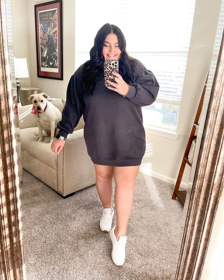 Garota tirando foto em frente ao espelho com celular na mão. Ela está usando uma blusa de moletom cinza escuro como vestido, um tênis branco e sorrindo. Ela está na sala e, ao fundo, sentado em um sofá, há um cachorro.