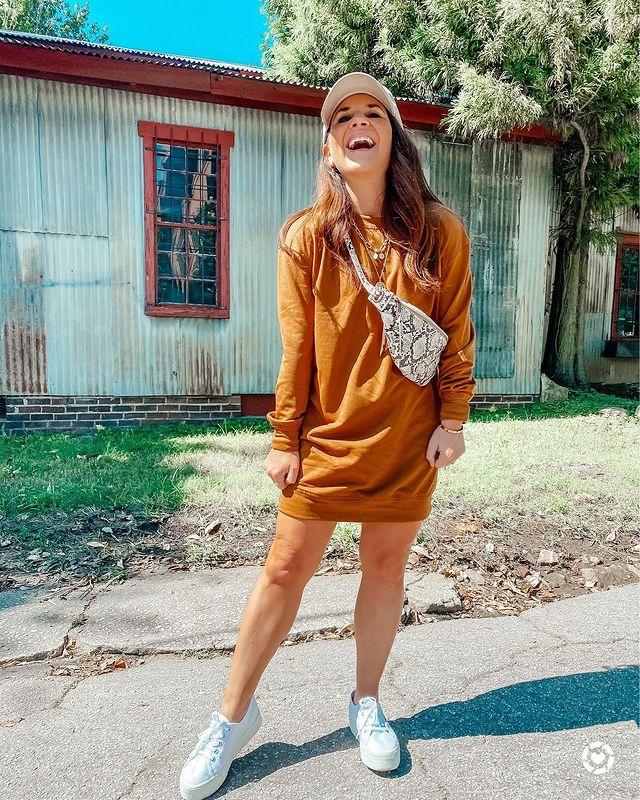 Garota usando blusa de moletom mostarda como vestido, tênis branco e pochete com estampa de cobra atravessada no corpo, além de um boné bege na cabeça. Ela está dando risada e olhando para cima.