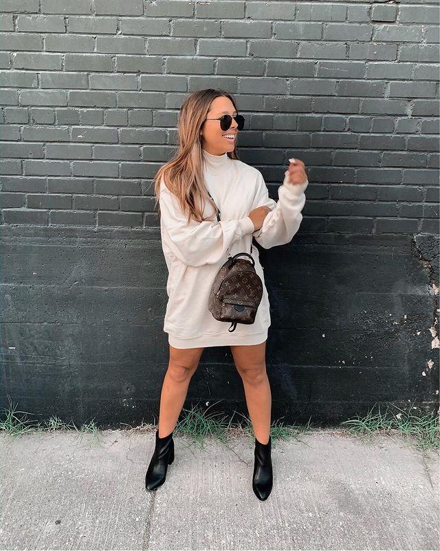 Garota usando blusa de moletom bege como vestido, bota preta de cano curto com bico fino, minimochila Louis Vuitton atravessada no corpo e óculos de sol. Ela está olhando para o lado, sorrindo, com uma das mãos apoiada no outro braço.