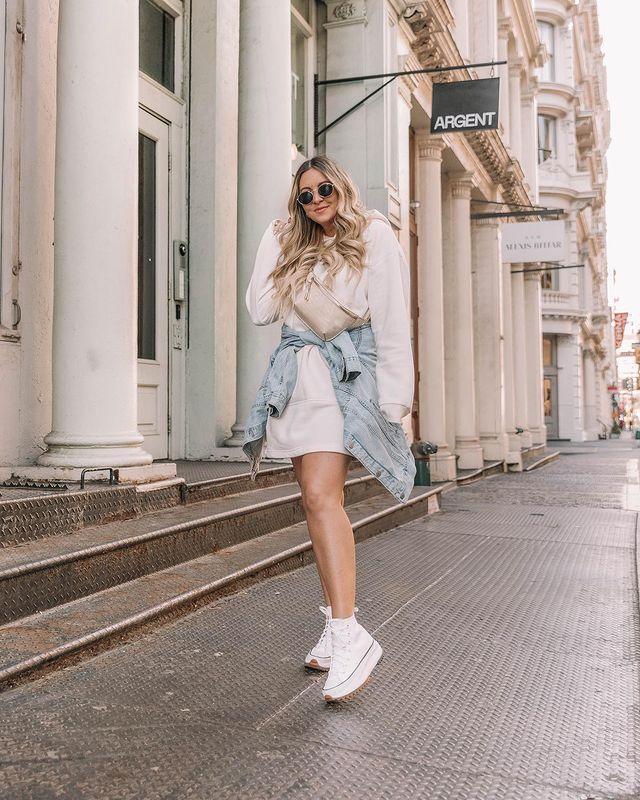 Garota usando blusa de moletom bege como vestido, tênis branco e jaqueta jeans amarrada na cintura. Ela está com uma pochete bege atravessada no corpo, usando um óculos de sol e com uma das mãos no cabelo enquanto sorri.