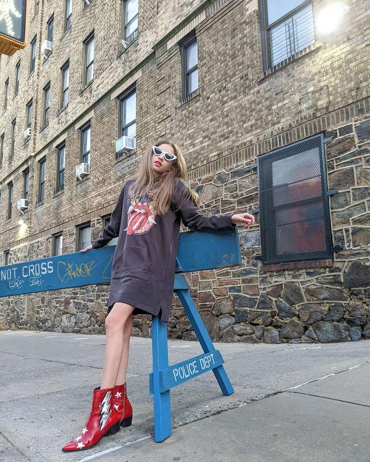 Garota usando vestido de moletom cinza com a língua dos Rolling Stones estampada e botinha vermelha country de cano curto, além de óculos de sol.