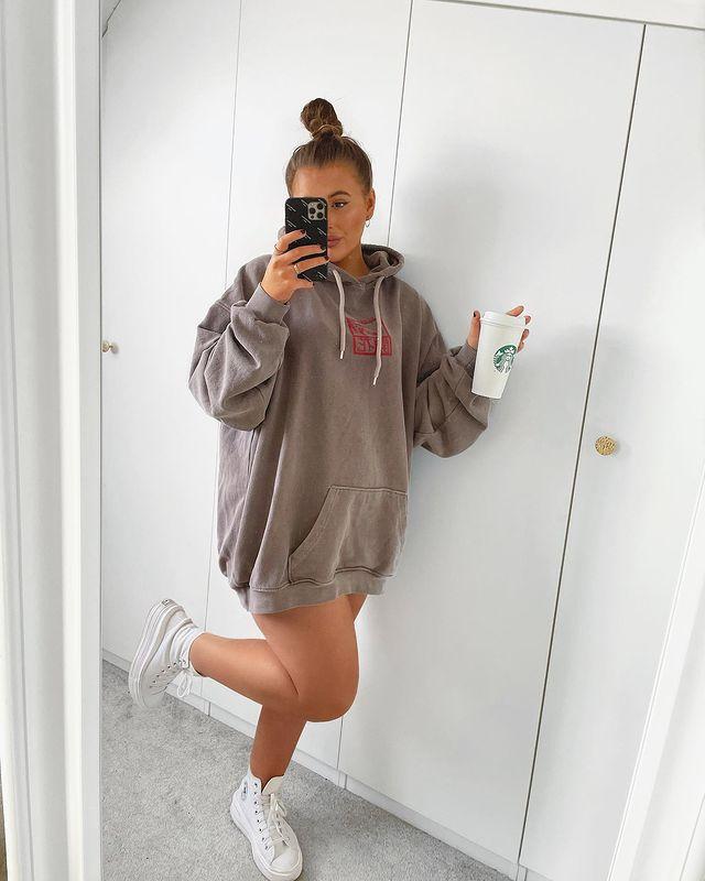 Garota em frente a um espelho tirando foto com o celular em uma das mãos e um copo branco de café na outra. Ela está usando uma blusa de moletom marrom como vestido e um tênis branco de cano alto, e uma das pernas está dobrada para trás.