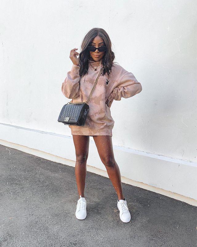 Garota usando blusa de moletom marrom como vestido, tênis branco e bolsa preta de alça de correntes atravessada no corpo, além de um óculos de sol. Ela está com uma das mãos na cintura, a outra perto do rosto e olhando por cima do óculos.