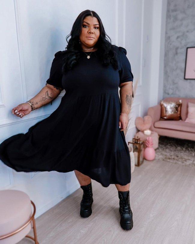 Jovem posando com lado do vestido levemente no ar, com expressão séria e os braços ao lado do corpo, usando vestido e coturno preto.