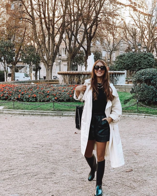 Jovem com sobretudo branco, meia calça, bota preta, short e blusa, usando óculos preto, com uma mão no bolso.