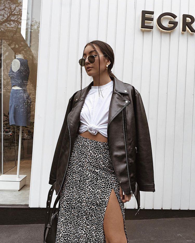 Garota usando camiseta branca com nózinho na frente, jaqueta de couro por cima, saia com estampa de oncinha e óculos de sol redondos. Ela está olhando para o lado com expressão facial séria e segurando uma bolsa preta com uma das mãos.