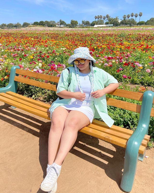 A mulher está sentada em um banco próxima a um jardim. Ela veste um chapéu branco com flores azuis, cropped azul claro com uma camisa verde menta como sobreposição, saia branca, tênis branco e óculos de sol com lentes amarelas. Ela olha para a câmera e sorri.