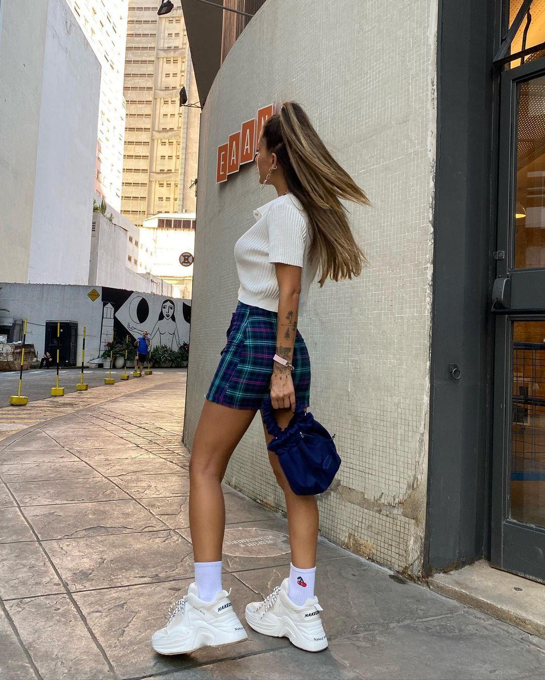 A mulher está em uma rua. Ela veste uma camiseta polo branca, saia azul com estampa xadrez e um tênis plataforma branco. Ela está de perfil para a foto.