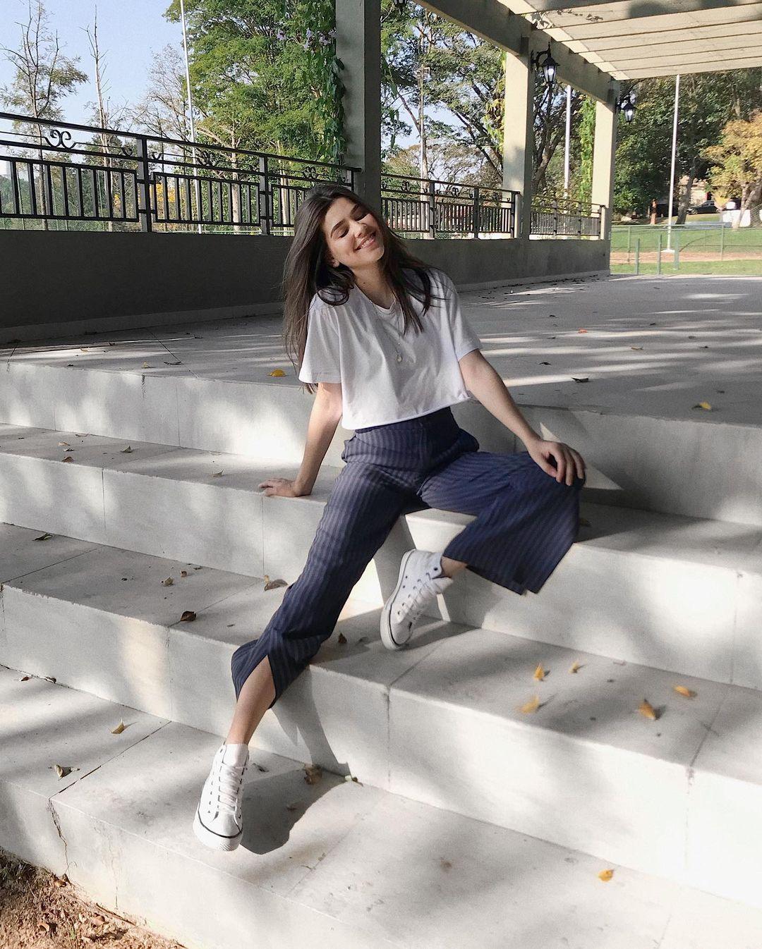 A mulher está sentada em uma escada. Ela veste uma camiseta branca, calça de alfaiataria azul e tênis de cano alto branco. Ela está de olhos fechados sorrindo.