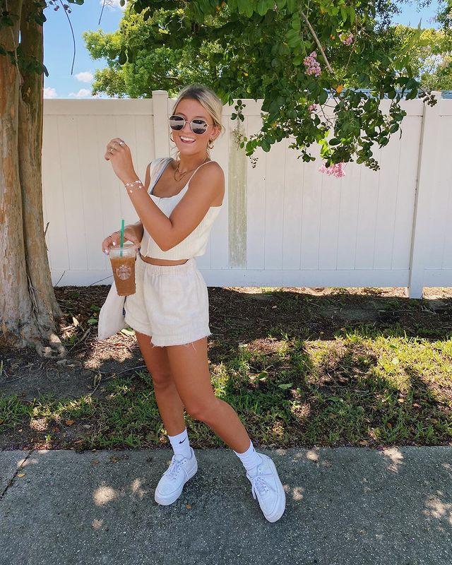 A mulher está próxima a uma árvore. Ela está vestindo um cropped e shorts off white, tênis branco, óculos de sol e cabelo preso. Ela olha para a câmera sorrindo.