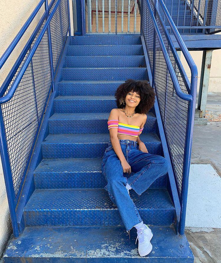 Mulher sentada em uma escada azul. Ela usa um cropped listrado e colorido, calça wide leg azul, um tênis branco e o cabelo crespo solto. Ela olha para a câmera sorrindo.