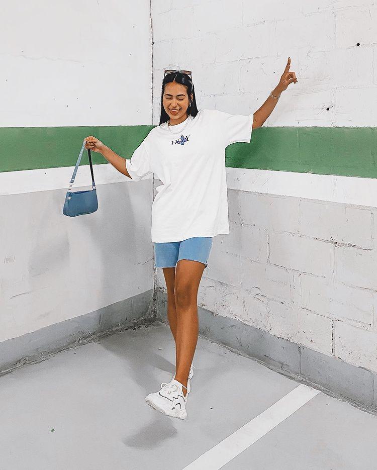 Foto de uma mulher em um estacionamento. Ela usa uma camiseta oversized branca, bermuda jeans, tênis branco e shoulder bag azul. Ela faz pose com a língua para fora e está de olho fechado.