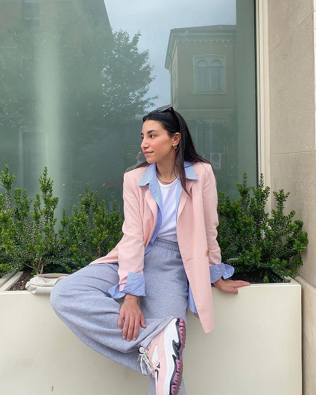 Foto de uma mulher sentada em um vaso de plantas grande. Ela usa uma camiseta branca, blazer rosa com azul, calça moletom cinza e tênis branco com rosa. Ela olha para o lado e sorri.