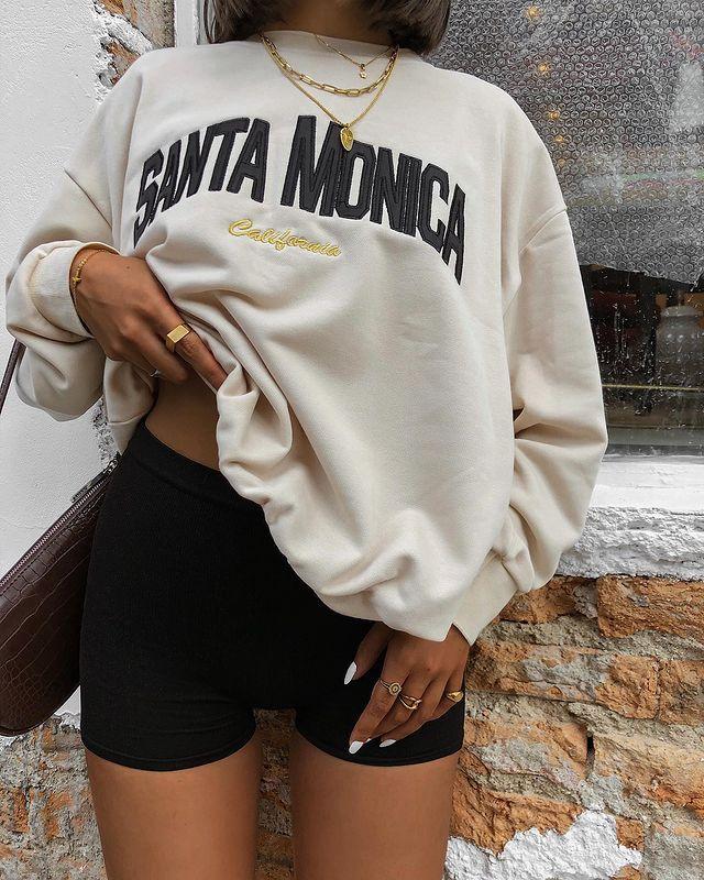 Foto apenas do look de uma mulher. Ela veste um biker shorts preto, moletom vintage bege e bolsa baguete na cor marrom.