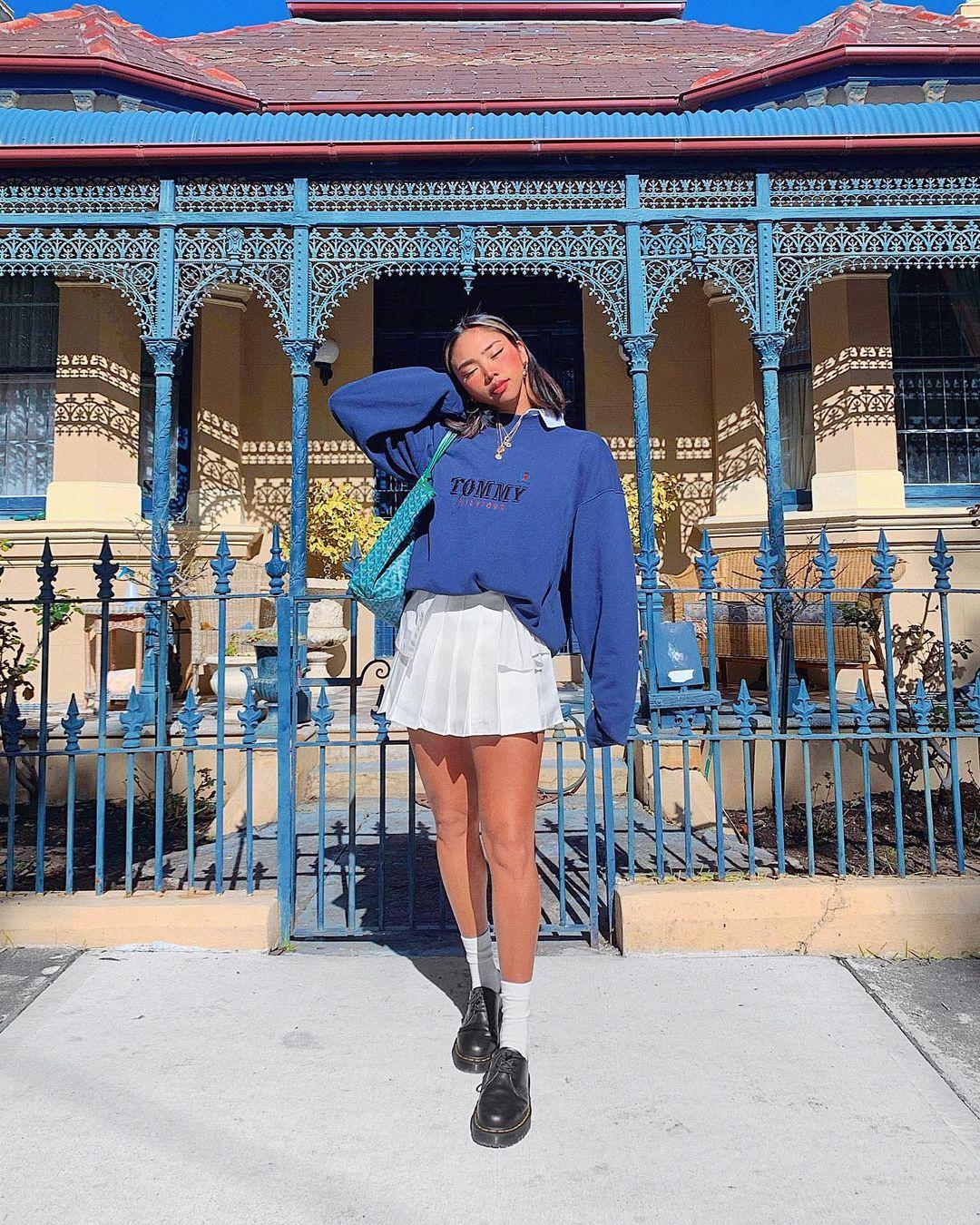 Foto de uma mulher em frente a uma casa com o portão azul. Ela usa um moletom vintage azul, saia colegial branca, sapato preto com meia branca. Ela está de olho fechado e cabeça apoiada no braço direito.