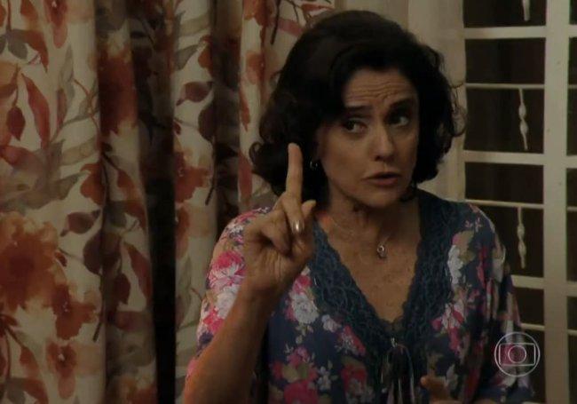 Marieta Severo interpretando Dona Nenê. A atriz usa uma blusa estampada e está com o dedo indicador levantado. Ao fundo, aparece uma cortina florida.