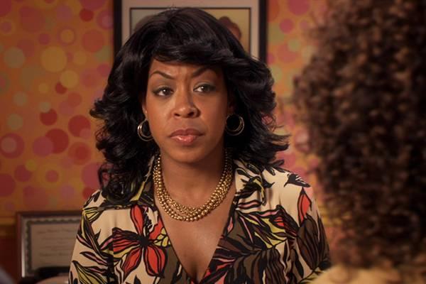 Personagem de Rochelle, de Todo Mundo Odeia O Chris, usando uma blusa estampada e olhando para outra mulher durante uma conversa. Ao fundo, aparece um quadro e um papel de parede florido.