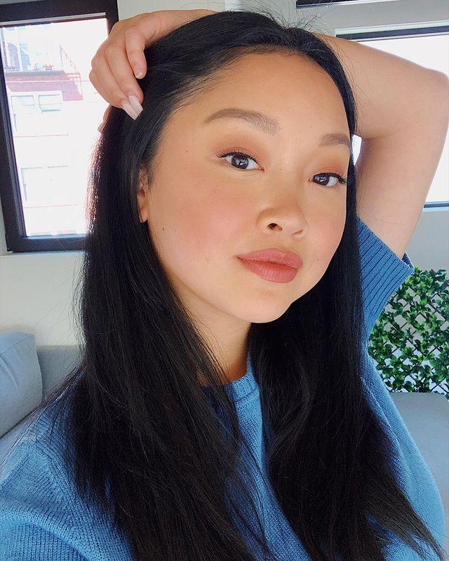 Selfie da atriz Lana Condor. Ela usa uma camiseta azul, cabelo solto, make natural com batom nude. Ela olha para a câmera, segura a cabeça com a mão esquerda e sorri para a foto.