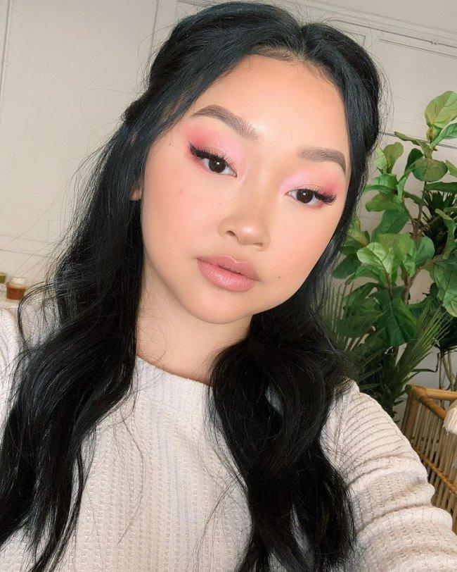 Selfie da atriz Lana Condor. Ela usa uma blusa branca, cabelo meio preso e maquiagem com sombra rosinha e delineado gatinho. Ela olha para a câmera e não sorri.
