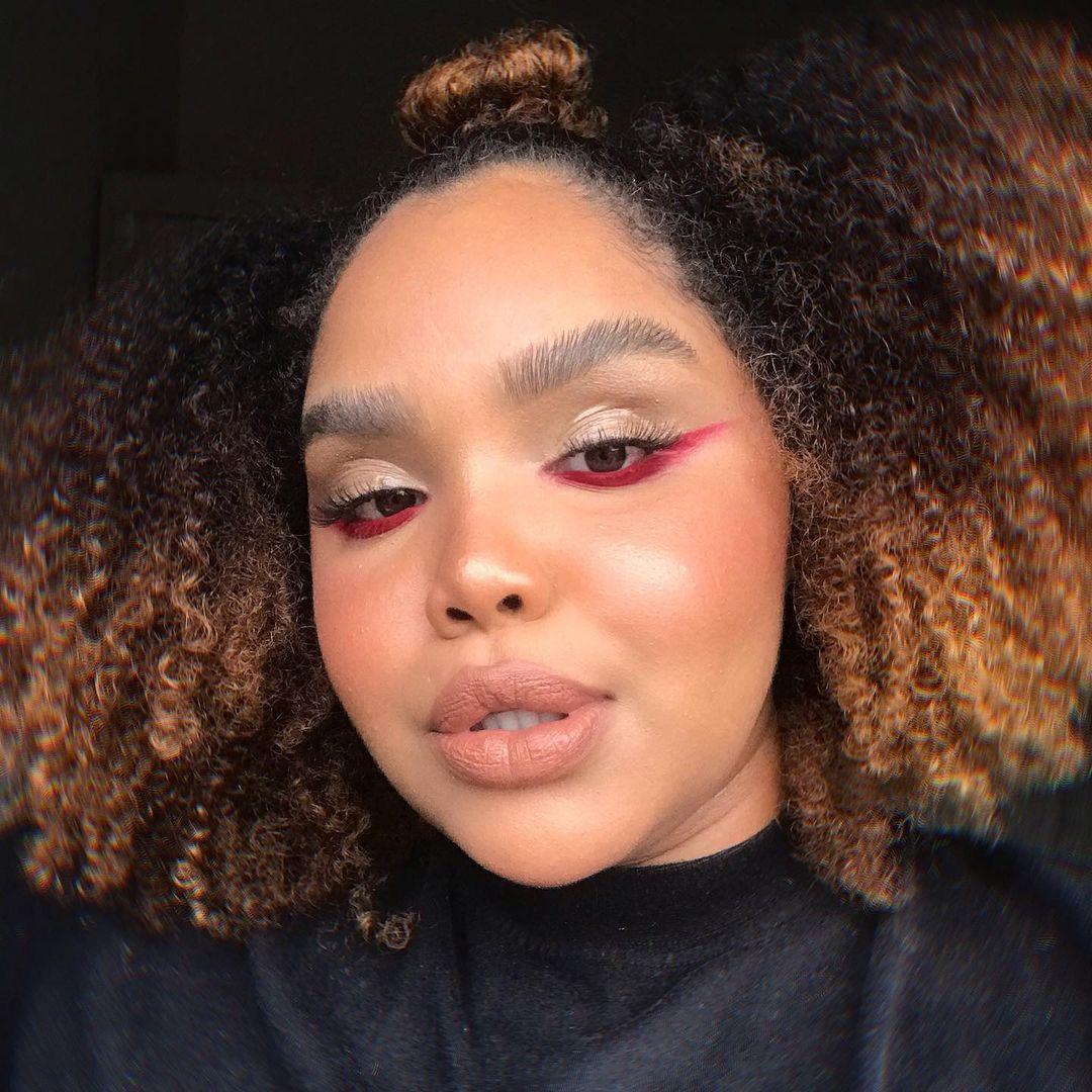 Garota usando maquiagem com delineado vermelho invertido rente aos cílios inferiores. Ela usa uma camiseta preta, seu cabelo é crespo e sua expressão facial é séria com os lábios levemente separados.