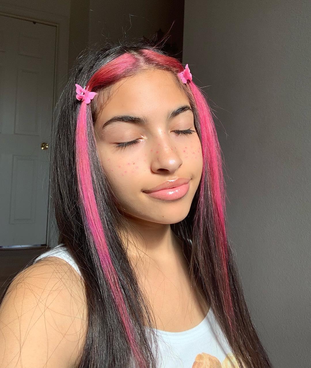 Garota sorrindo com os olhos fechados para foto. Ela está vestindo uma regata branca, gloss nos lábios e cabelo preto com mechas frontais cor-de-rosa presas em dois acessórios de borboletas.