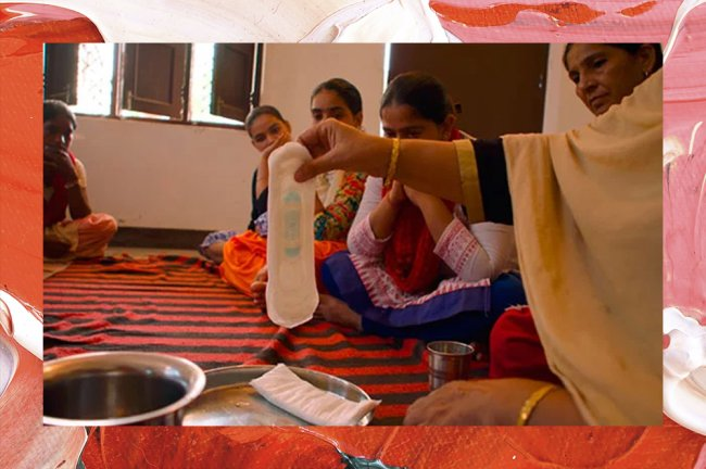 Adolescentes indianas olham para um absorvente descartável que está sendo mostrado por uma mulher mais velha