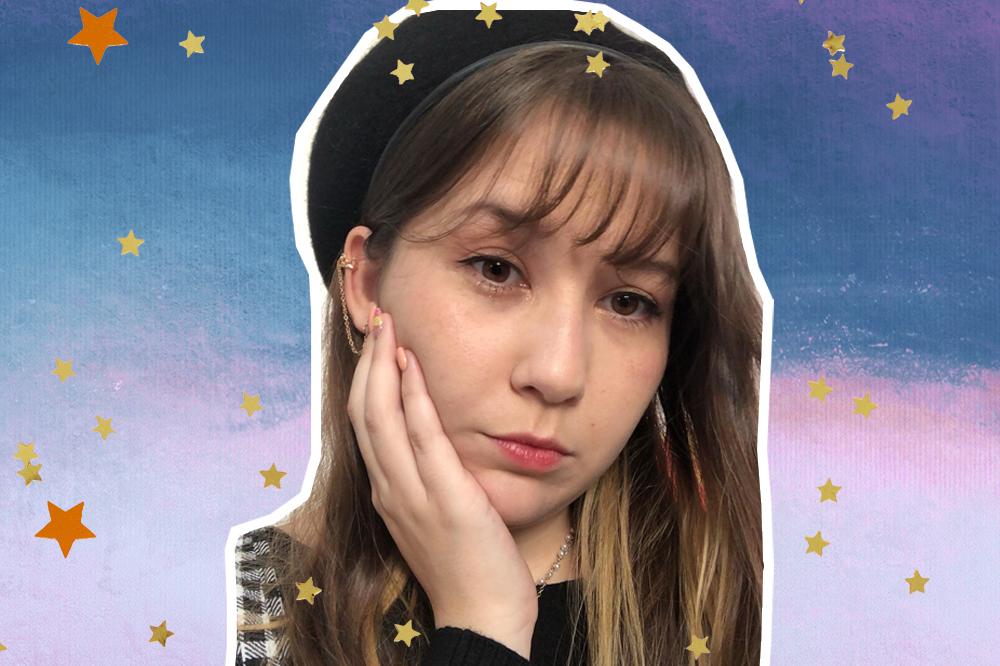 Colagem com selfie de Midori com a mão no rosto e expressão séria; ela usa franja e um chapéu como acessório; o fundo da imagem é uma textura em tons de azul, rosa e branco com estrelas amarelas e laranjas de decoração