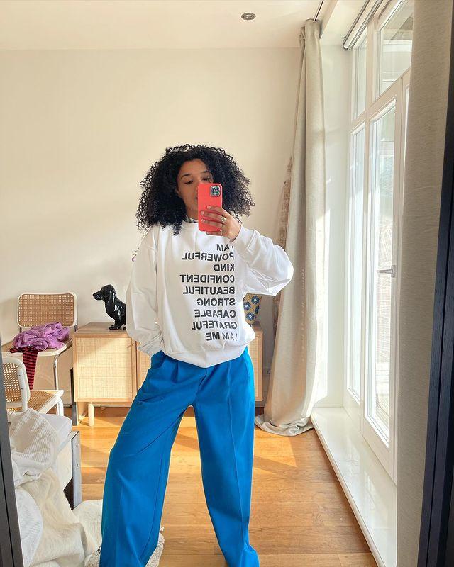 Selfie no espelho de uma mulher. Ela usa um moletom branco baggy, calça baggy azul e está com o cabelo solto. Ela não sorri para a foto.