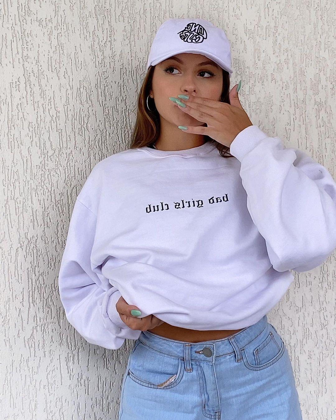 Foto de uma garota em frente a uma parede branca. Ela usa um moletom branco baggy, calça jeans e boné branco. Ela olha para o lado está com a mão na boca.