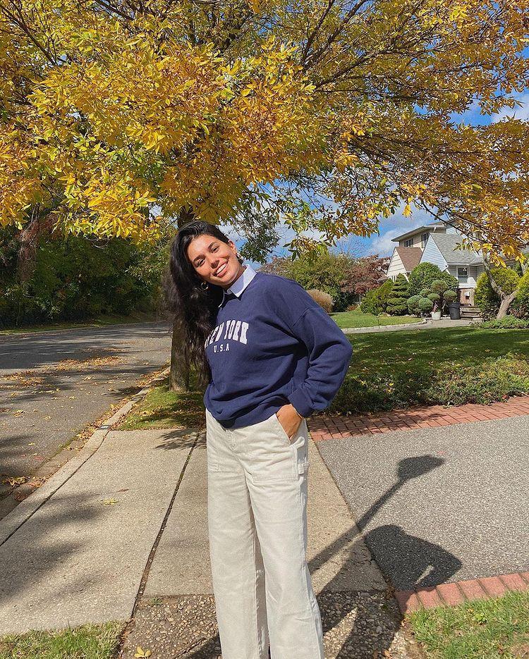 Foto de uma mulher na calçada. Ela usa um moletom vintage azul e calça bege. Ela olha para a câmera e sorri.