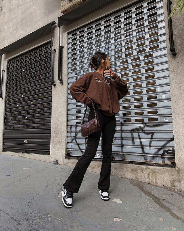 Foto de uma mulher na calçada. Ela veste um moletom vintage marrom, calça bailarina preta e tênis preto e branco. Ela olha para o lado e faz pose.