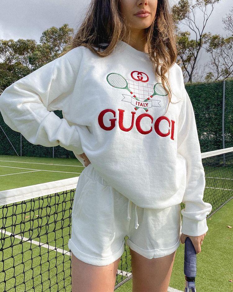 Foto da roupa de uma mulher. Ela veste um short de moletom branco, moletom vintage da Gucci na mesma cor. Ela está em uma quadra esportiva de tênis.