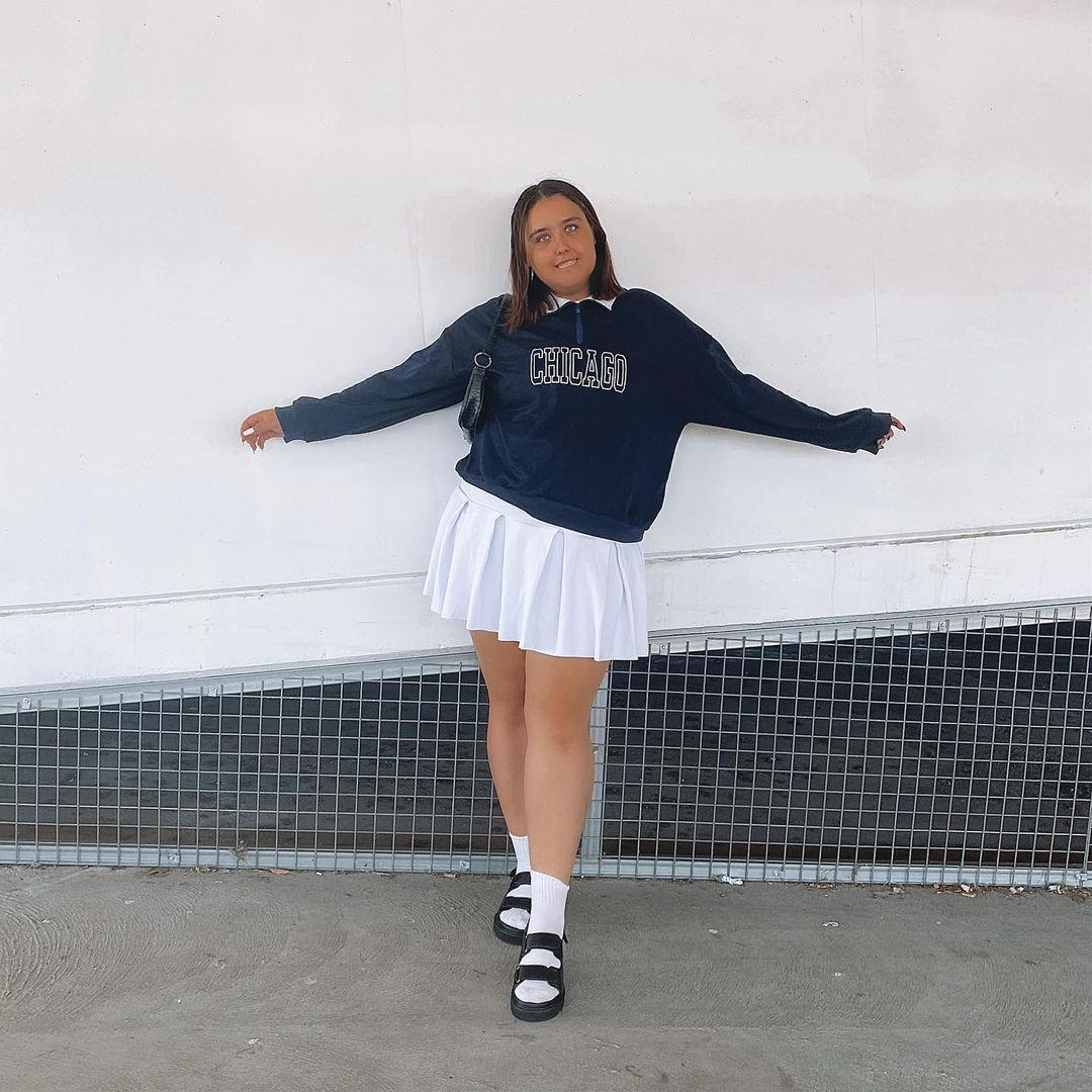 Foto de uma mulher com o fundo de uma parede branca. Ela usa um moletom vintage azul escuro, saia colegial branca e papete preta com meia branca. Ela olha para a câmera e sorri.