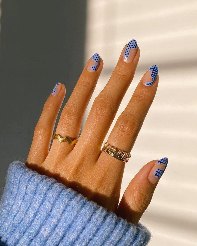 Foto de uma mão com anéis no dedo anelar e indicador. As unhas estão pintadas com uma nail art ondulada, estampa xadrez e bolinhas.