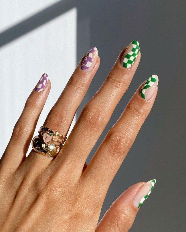 Foto de uma mão com anéis no dedo anelar. As unhas estão com uma nail art ondulada na estampa xadrez.