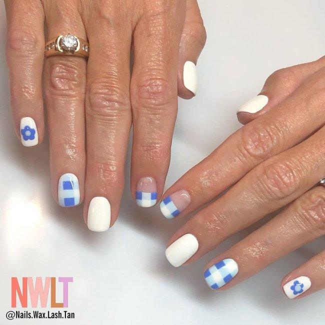 Foto de duas mãos com anel no dedo anelar da mão direita. Ambas as mãos estão com uma nail art xadrez azul e branco.