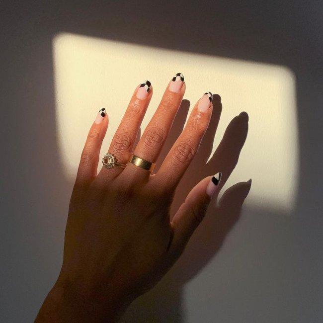 Foto de uma mão com anéis dourados no dedo anelar e médio. Com nail art xadrez preto e branco como francesinha.