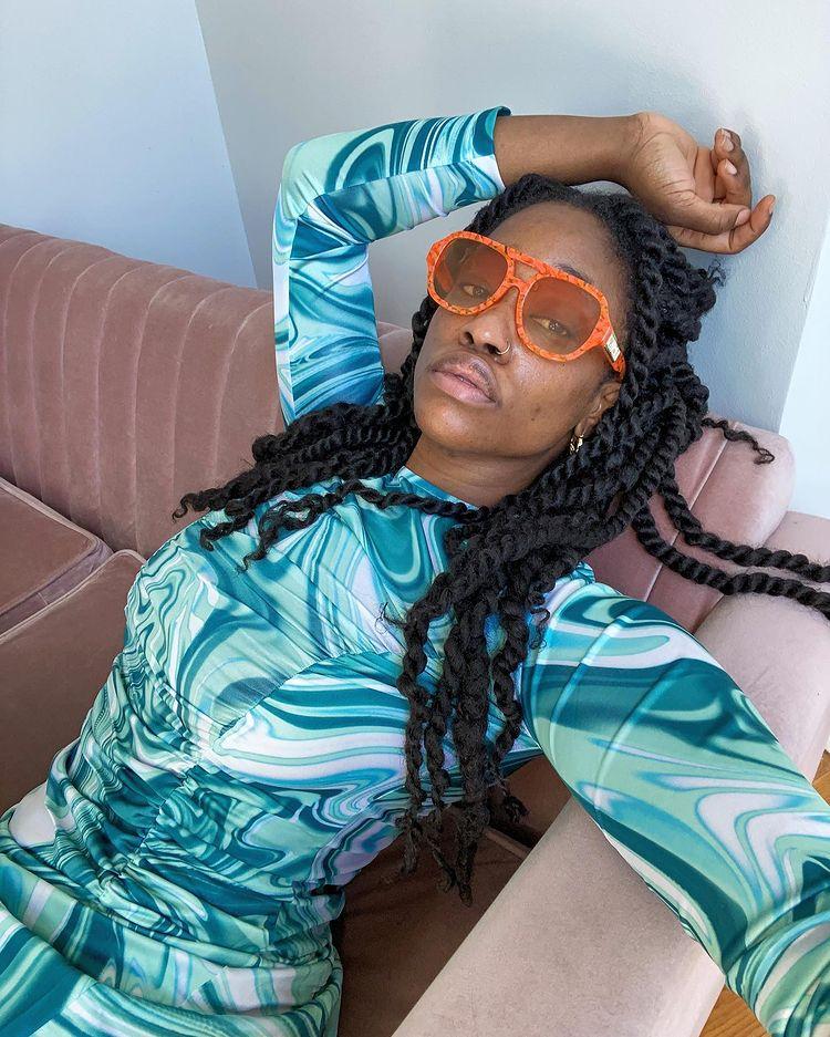 Mulher sentada em um sofá com a cabeça apoiada e inclinada para cima, com uma das mãos na cabeça. Ela está usando um vestido de manga comprida em tons de azul, um óculos de sol laranja e sua expressão facial é séria.
