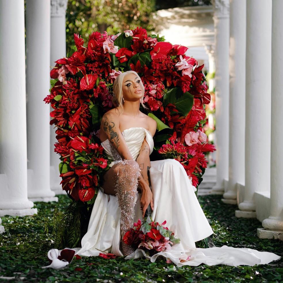 Pabllo Vittar sentada em cadeira decorada com rosas vermelhas, ela usa um vestido de noiva branco e segura um buquê de flores; a maquiagem da cantora é escura e seu rímel está borrado, indicando que ela teria chorado